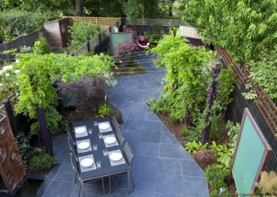 Diagonally designed contemporary garden, slate paving, table and chairs, screens