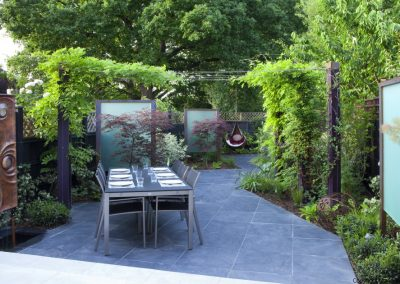 Diagonally designed town garden, wisteria climbing on pergola, table and chairs, slate paving, Acer palmatum 'Burgundy Lace', perspex screens, copper water feature