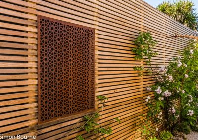 Corten steel panel set within trellis work